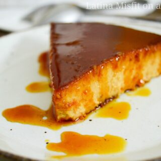 caramel drizzled over pumpkin flan on a white dish