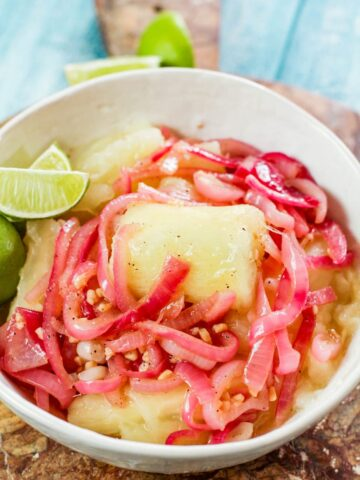 yuca with mojo in a white bowl