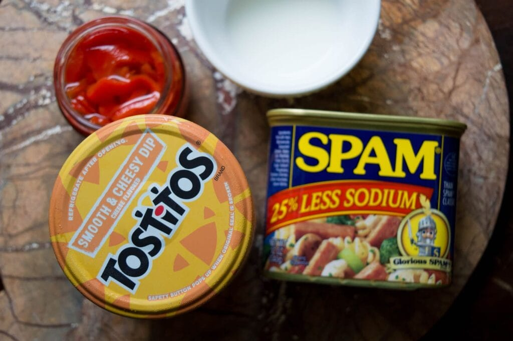 can of spam, cheese dip, and open pimentos on a marble surface