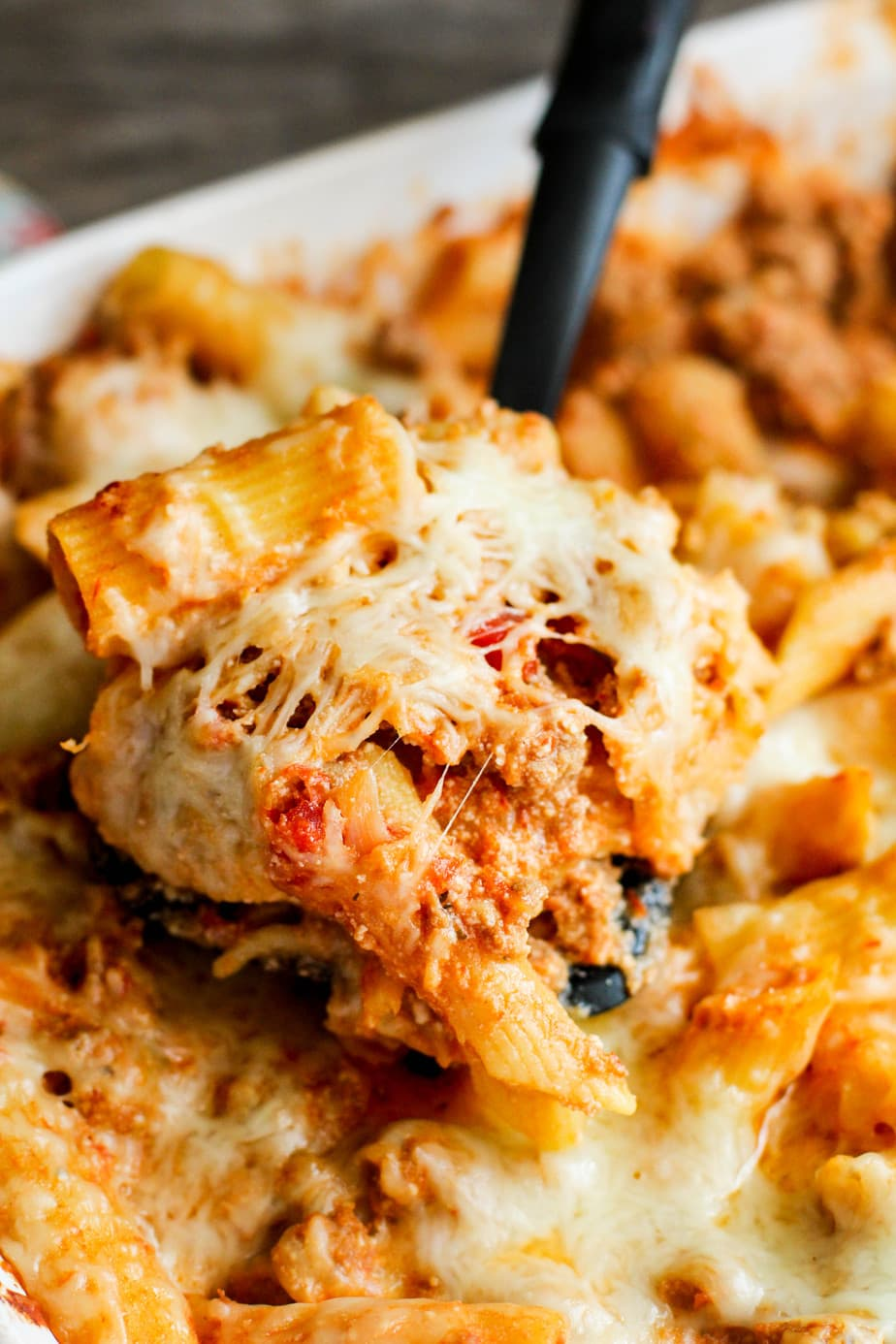 cheesy baked pasta being held by a spoon