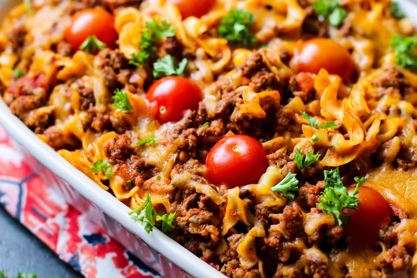 sausage and pasta bake with big fresh tomatoes in a pan
