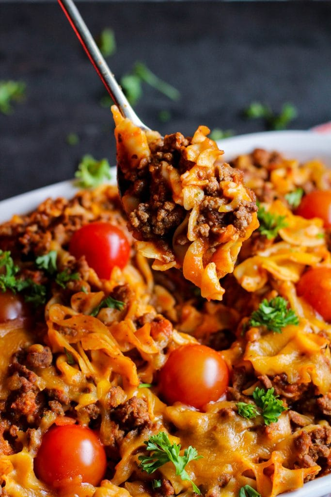 Pasta bake with a spoon and tomatoes