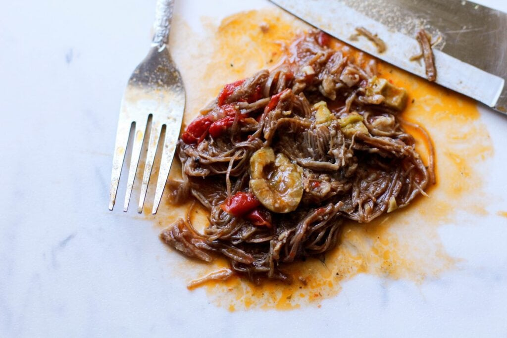 Ropa Vieja shredded on a cutting board with a fork and knife