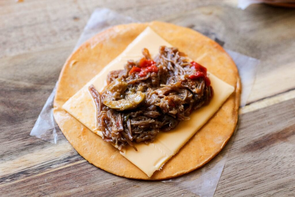 Unrolled ropa vieja empanada on a cutting board