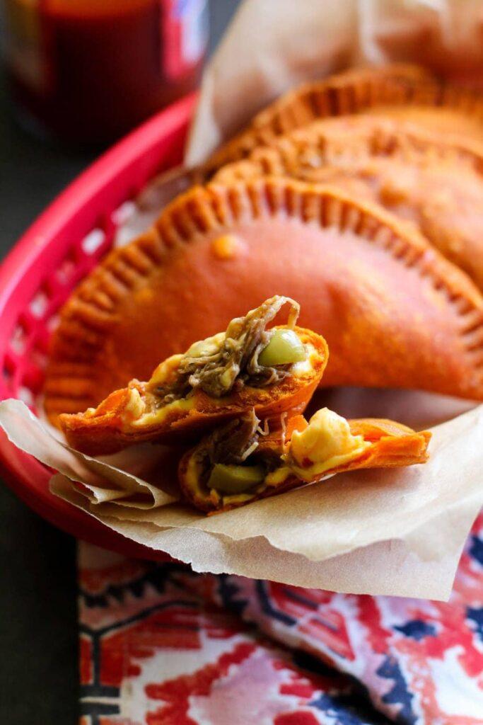 Empanada cut open in a red plastic basket with whole empanadas