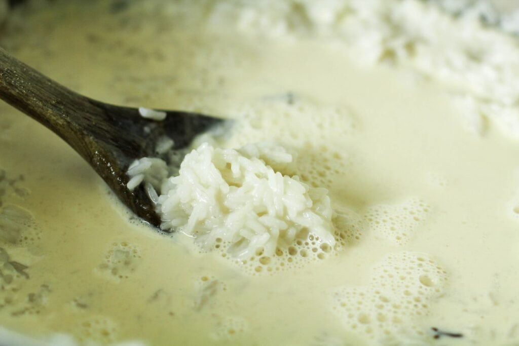 rice surrounded by milk in a pot with a wooden spoon