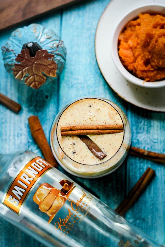 Coquito with vodka on a wooden blue background