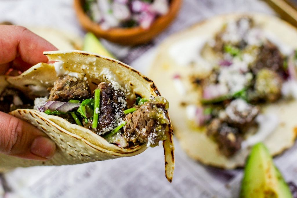 barbacoa tacos held in the air