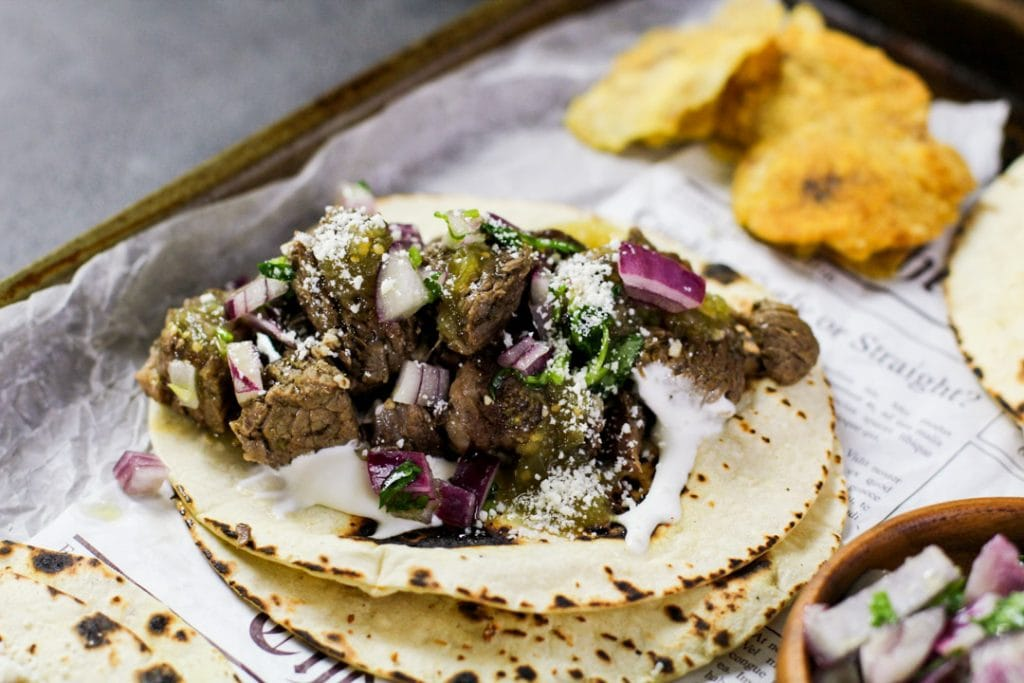 horizontal image of a steak taco on parchment paper
