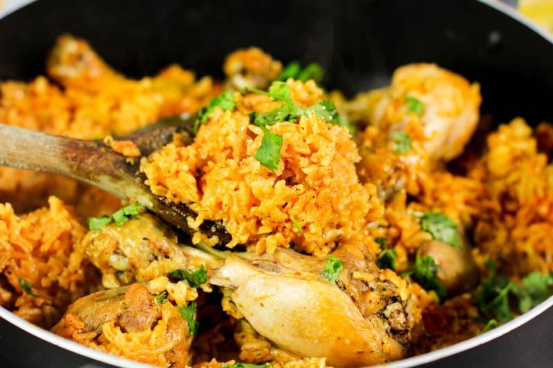 arroz con pollo in a black pan with a wooden spoon.