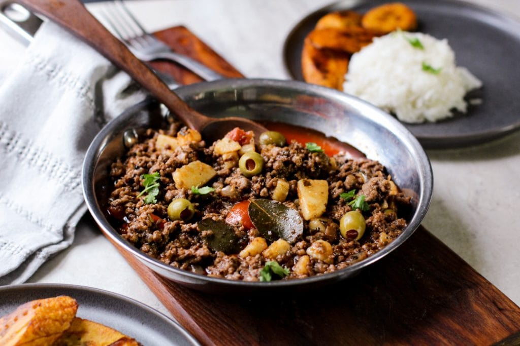 picadillo in a pan with a wooden spoon