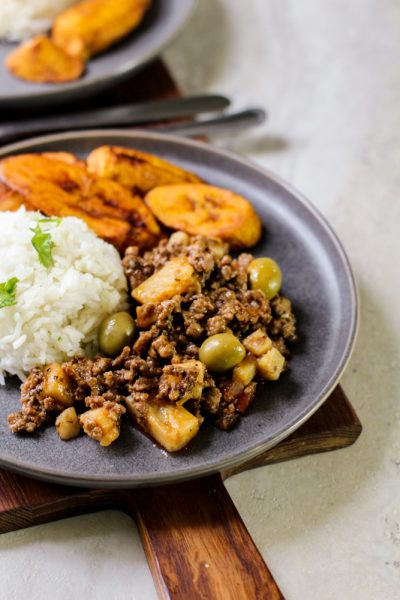 picadillo with write rice and plantains on a gray plate