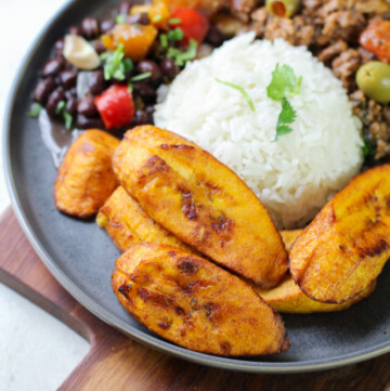 fried plantains on a gray plate with rice and beans