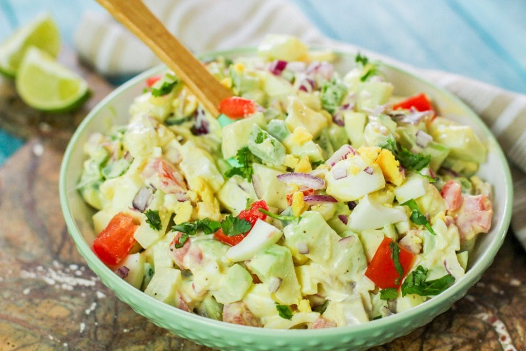chayote egg salad with a wooden spoon in a bowl