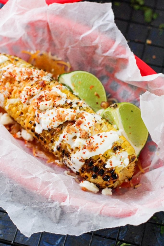 street corn with bacon and lime wedges