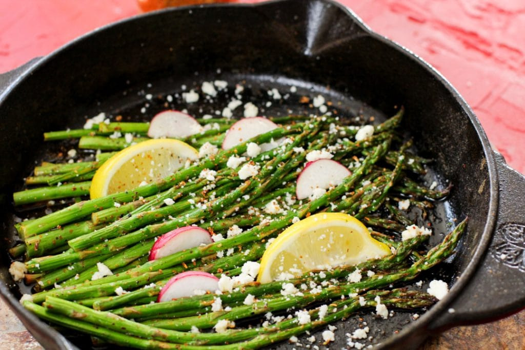roasted asparagus with cheese and lemon wedges