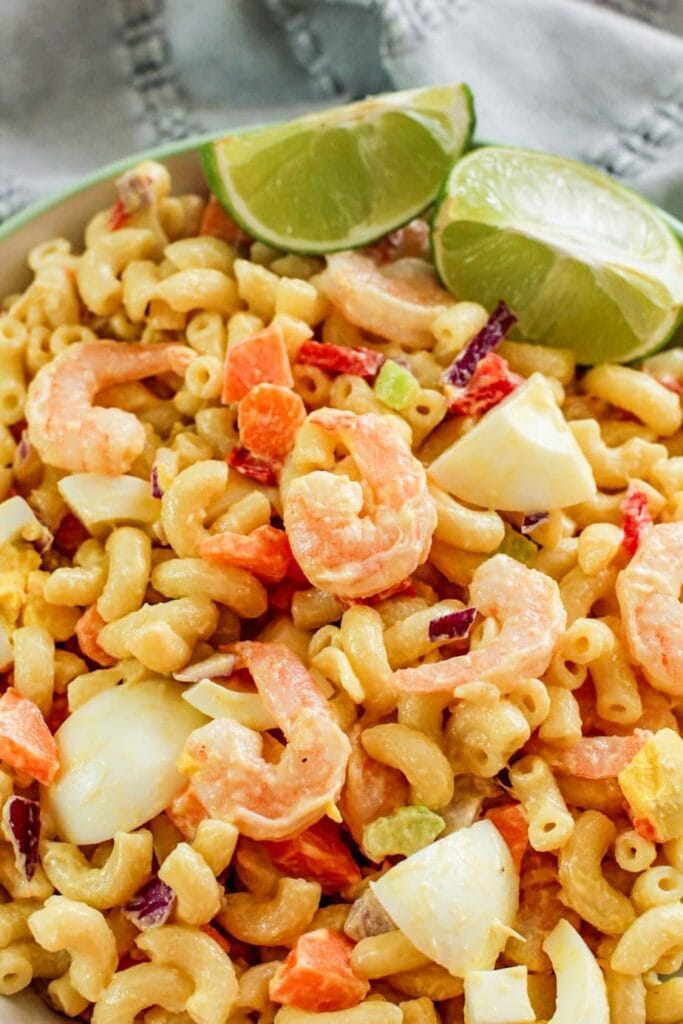 shrimp with limes in a bowl with macaroni noodles