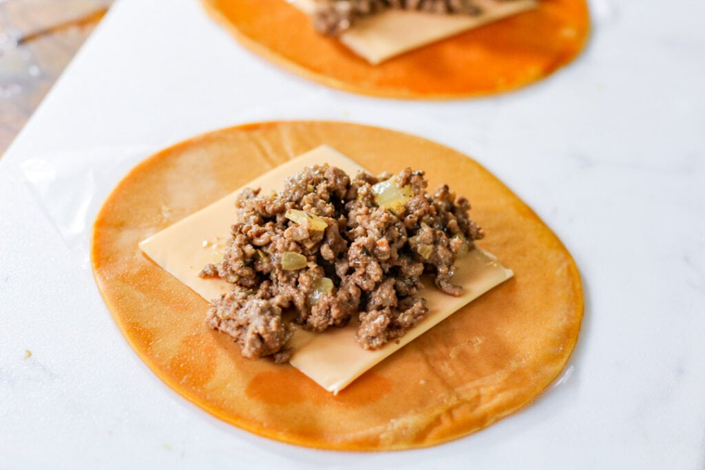 open disc with slice of cheese and picadillo