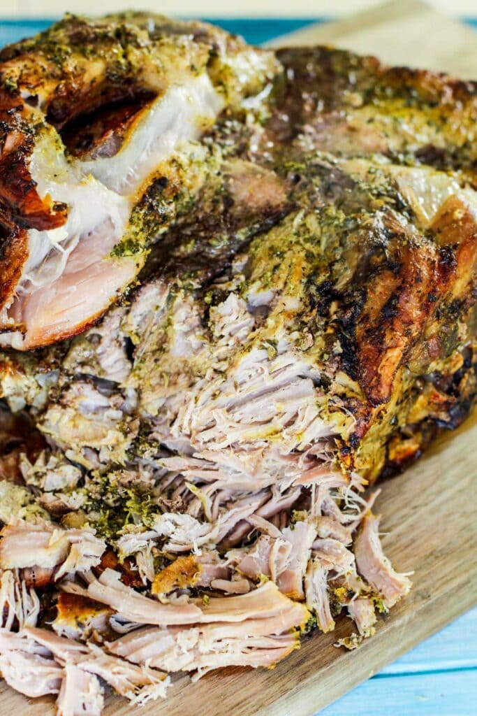 shredded pernil on a cutting board