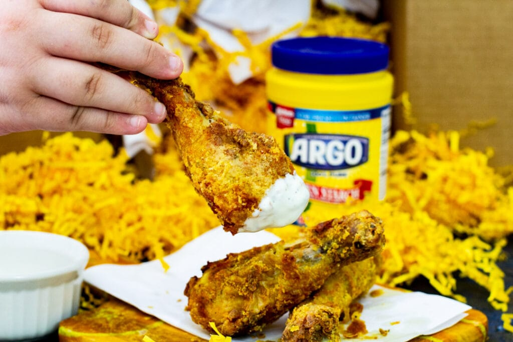 Fried chicken being dipped into ranch.