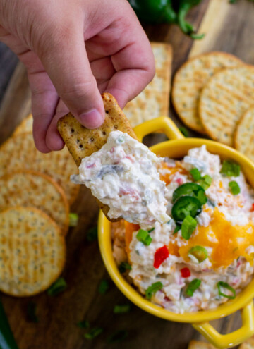 dipping cracker into a bowl of jalapeno dip