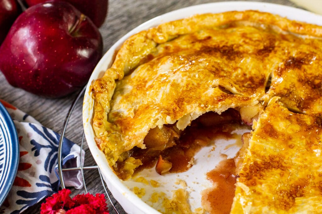 baked apple pie in a white pie plate