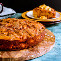 Pumpkin apple cake on a brown serving platter.
