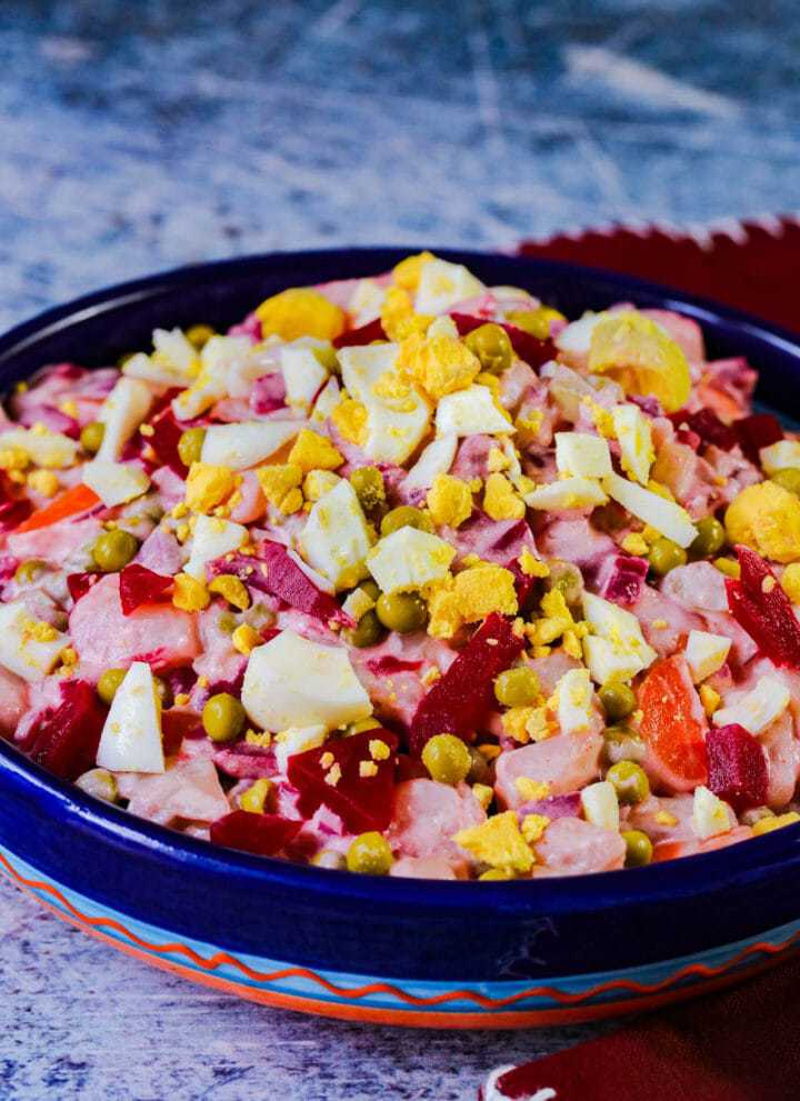 ensalada rusa in a blue bowl with eggs on top