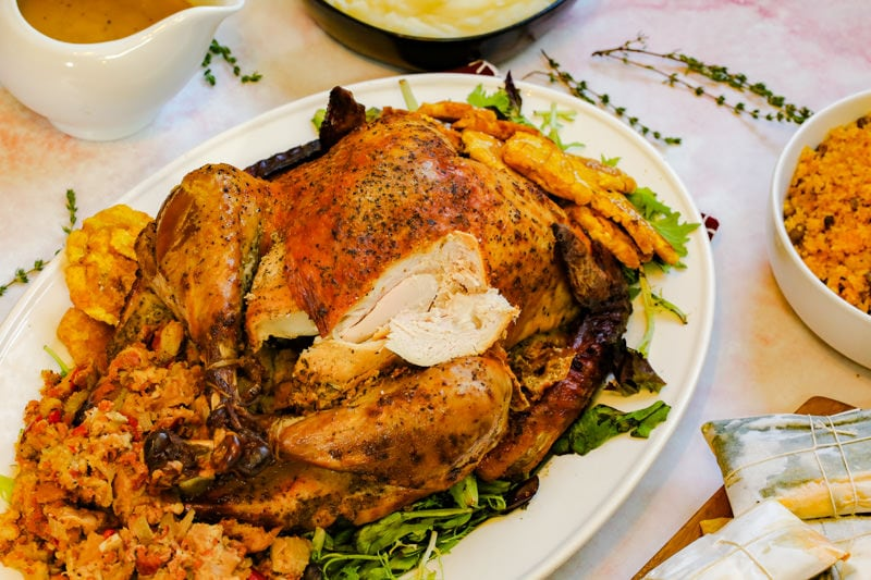 Puerto Rican turkey on a white platter with a chunk cut out
