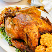 Whole turkey on a white platter with plantains