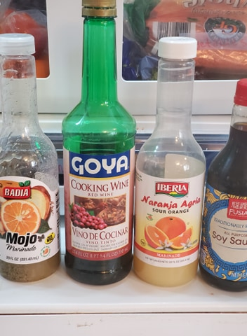 containers of cooking wine, soy sauce, and mojo in a fridge