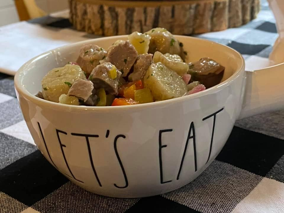 a let's eat bowl filled with gizzards and bananas over a white and black cloth